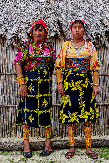 Guna women in traditional dress.  Note mola panels on the front of their shirts.   And wini beads around their legs