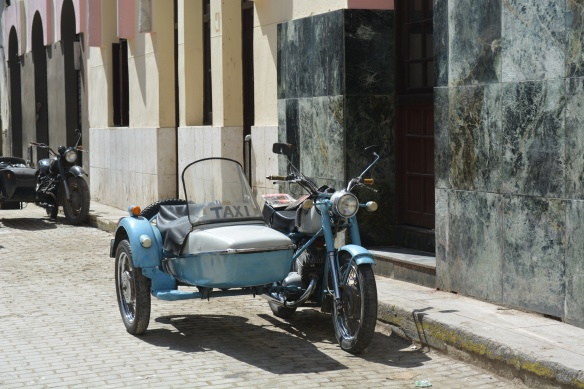 Along with all the classic 1950s American cars are lots of 19? motorcycles with sidecars