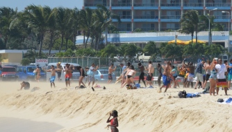 Idiots on the airport beach been blown over by the landing plane.